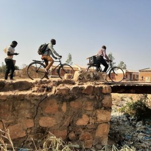Three African missionaries riding bikes into a village