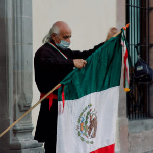 A man adjusting the Mexican flag